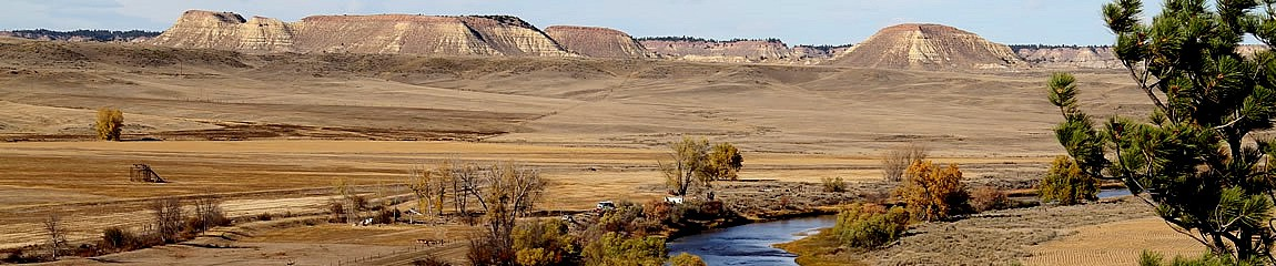 Brown grass buttes with a river flowing between them